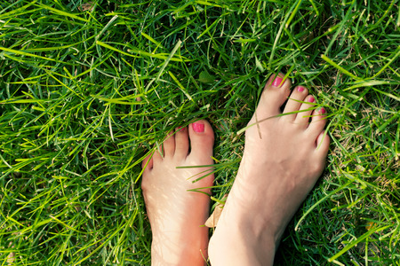 Foot over green grass. photo