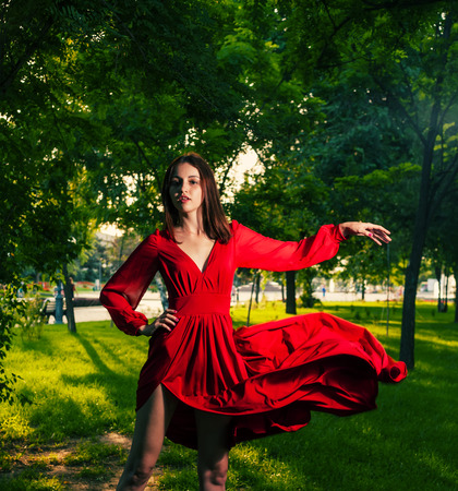Young brunette dancing in red dress outdoors on nature . Portrait of dancing woman at forest photo