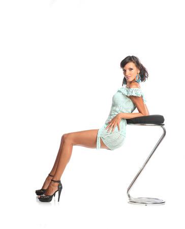 posa sexy: Bella giovane donna latino seduto su uno sgabello con carino posa sexy su bianco