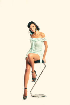 Attractive black haired woman sitting on a chrome bar stool. photo