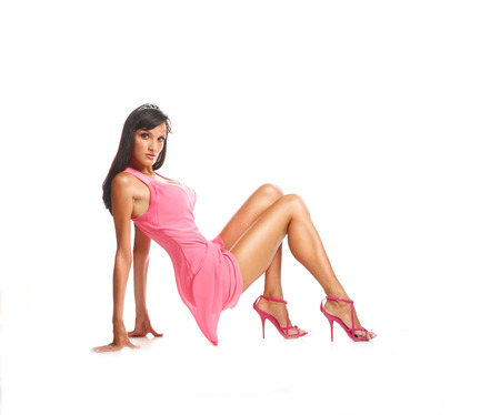 Portrait of beautiful brunette model sits on the floor in pink dress, photo
