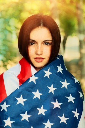Serious young woman warp in US american flag photo