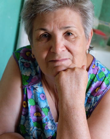 Old women thinking indoors with her hand on chin photo