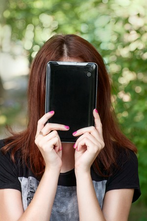 REdhead women hide her face by tablet PC  photo