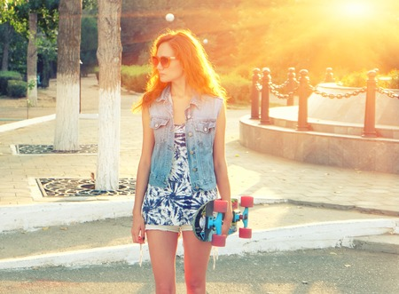 Pretty young woman backlit  standing with skateboard in her hands backlit by sunset photo