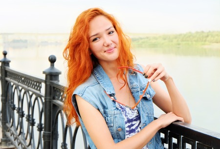 Smiling red haired women standing near river. photo