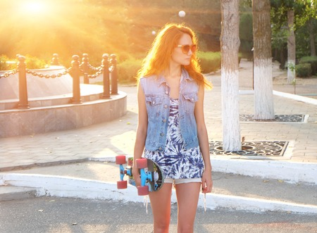 Beautiful young woman standing with skateboard in her hands backlit by sunset photo