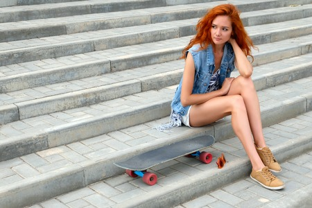 Beautiful young woman sitting near a skateboard. photo