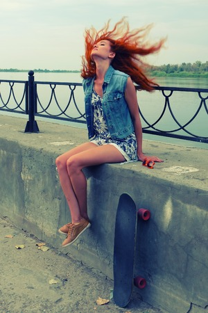 Young women sitting with her skate board on concrete street parapet with her red hair flying in the wind photo