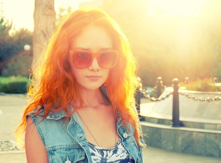 Portrait of young beautiful red haired and elegant stylish girl backlit with fence at background photo