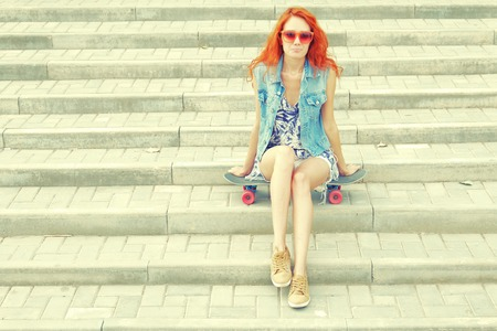 Beautiful redhead young woman sitting over a skateboard on street stairs as background photo