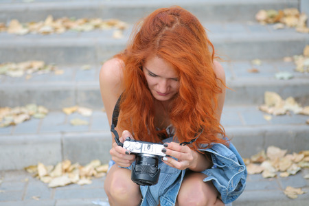 Young redhead woman photographer. Cute women halding modern camera in her hands and looking at screen inspect images photo