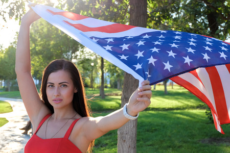 Serious young woman holding american flag flying by the wind photo