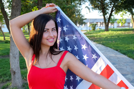 Happy young woman holding american flag in her hands. She weared in pretty red dress. photo