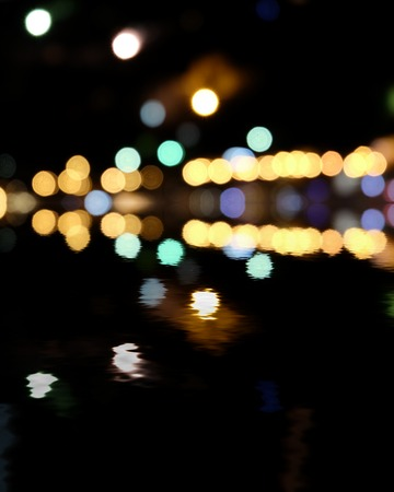 Yellow and green spots on black. Blurred city at night, bokeh background. Reflection of colorful lights in water and a lot of copyspace photo