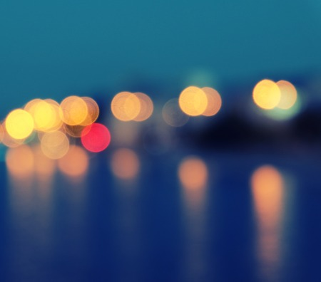Square image of a blurred city lights with bokeh effect reflected on water photo