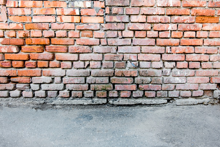 Red brick wall and a blacktop for copyspace backgrounds.