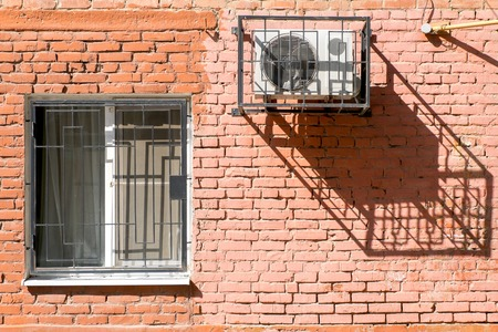 Window and air conditioner on a brick wall. photo