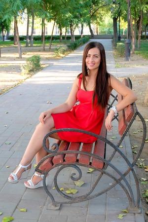 Beautiful fashionable girl sitting on park bench full body shot image photo