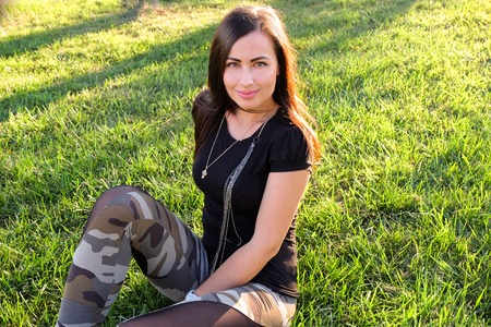 Brunette looking at camera and smiling. Carefree vitality freedom girl  in grass. photo