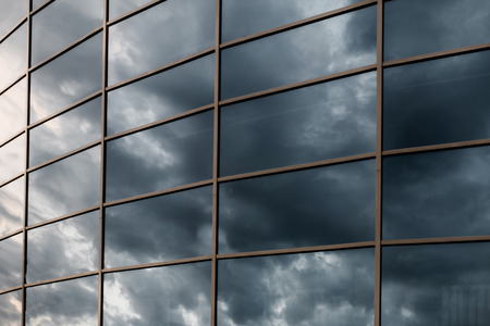 Glass skyscraper wall with reflection of dark stormy clouds at sunset. photo