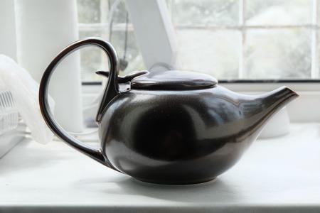 Brown asian teapot on the white windowsill side view photo