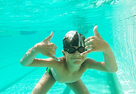 Portrait of a cute little boy swimming underwater and gesturing - OK sign and a lot of copyspace  photo
