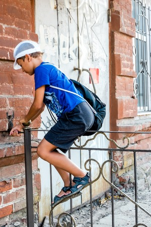 Child boy climbing over metal fence in a street, side view. photo