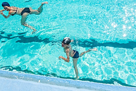 Mother giving son a swimming lesson in pool during summer a lot of copyspace photo