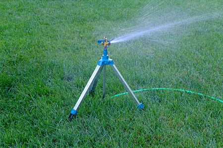 Mobile sprinkler system mounted on tripod working on fresh green grass. photo
