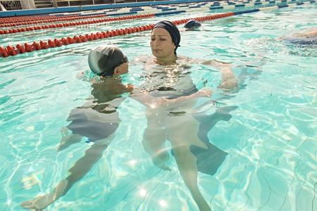 Son and mother in swimming pool. Mom giving son a swimming lesson in pool during summer. photo