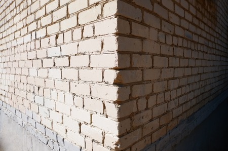 Wide angle view of the corner of a building made of white bricks, shadow and light sides, frame for text, a lot of copyspace photo
