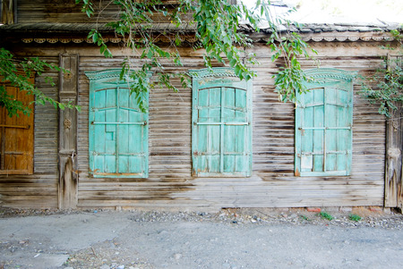 Thre green vintage windows of a old wooden house in Russia front view photo