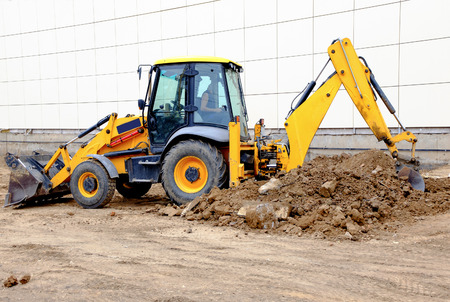 Yellow excavator working with a lot of soil photo