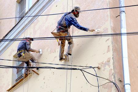 Two unrecognizable painters repair facade
