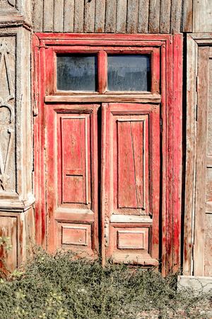 Aged red door with two glass windows on the top in old slum house in Astrakhan, Russia photo
