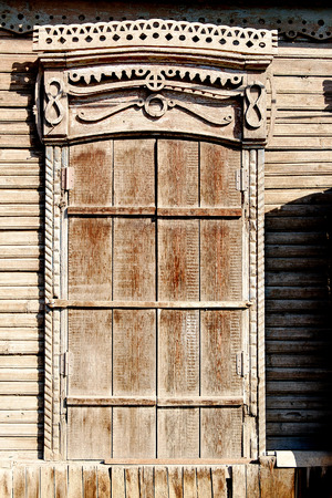 Aged brown  closed shutters window of a old wooden slum house in Astrakhan, Russia photo