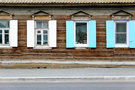 Wall of the aged wooden hut and fragment of pavement in Astrakhan, Russia. Four old vintage windows in traditional Russian style. Front view, open shutters. Vintage window of a old wooden house in Russia and a lot of copyspace photo