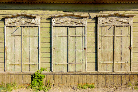 Three old vintage windows in traditional Russian style in Astrakhan, Russia. Front view, closed shutters. Vintage window of a old wooden house in Russia and a lot of copyspace photo