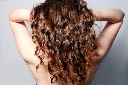 Closeup rear view of a curly womens hair. photo