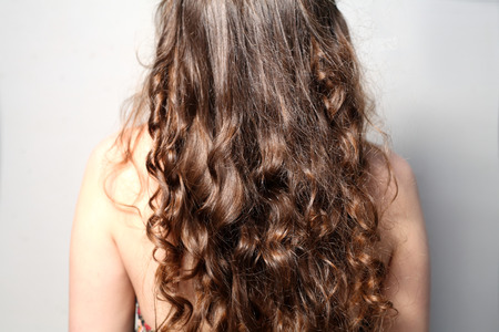 Back side view rear of young female curly hair.