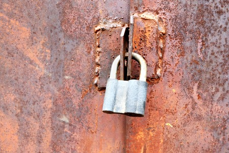 Closeup of the door lock on rusty metal stained gates. photo
