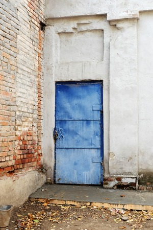 Blue vintage mediterranean door in obsolete wall and a lot of copyspace. photo