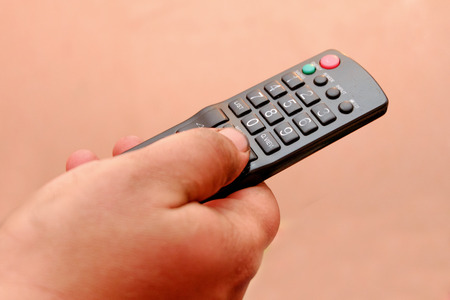 TV remote control in mens hand, a lot of copyspace photo