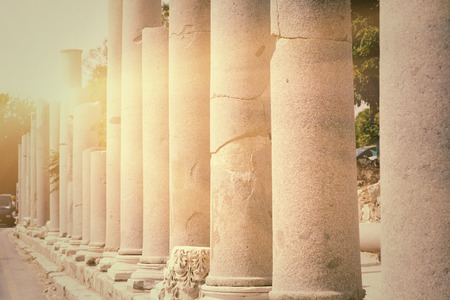 Row of pillars backlit in town Side (Turkey), ancient Roman architecture, ruins of aged castle, religious building in bright sun light photo