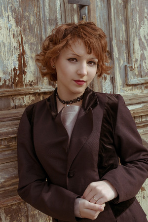 Retro portrait of red haired women in vintage coat agains obsolete wooden background. photo