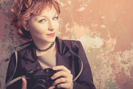 Redhead hipster woman taking photos with retro film camera outdoors. photo