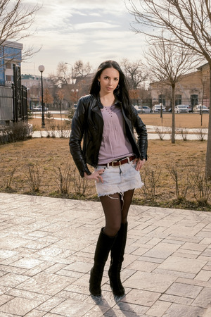 full figure: Full figure portrait of beautiful young woman in the park at fall standing alone in short skirt and black jacket. Toned colorized image. Stock Photo