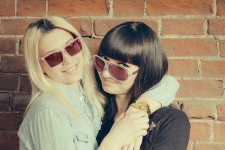 fiend: Close up fashion portrait of two girls hugs and having fun together, wearing stylish sunglasses, best fiend enjoy amazing time together Stock Photo