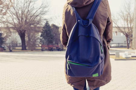 Rear view of hipster girl carring backpack on her back, copyspace.